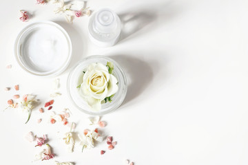 Foto op Plexiglas Spa Styled beauty composition. Skin cream, shampoo bottle, dry flowers, rose and Himalayan salt. White table background. Organic cosmetics, spa concept. Empty space, flat lay, top view, web banner.