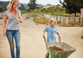 Mother and son pushing wheelbarrow with horse dung