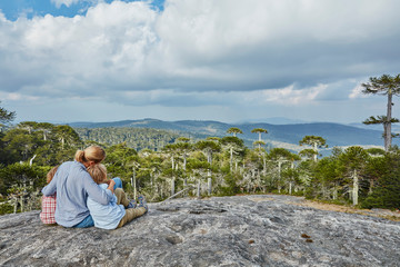 Chile, Puren, Nahuelbuta National Park, woman sitting with sons on boulder looking at Araucaria forest