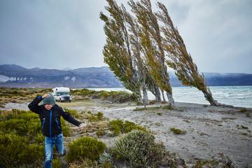 Argentina, Lago Posadas, boy running at the lake in storm