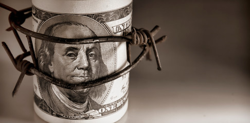 100 US Dollar bills wrapped with barbed wire as symbol of economic warfare, sanctions and embargo busting Wall mural