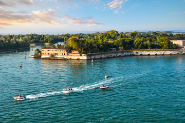 A group of small motor boats cruise past one of the outlying islands near Poveglia, in the waters off of Venice, Italy.