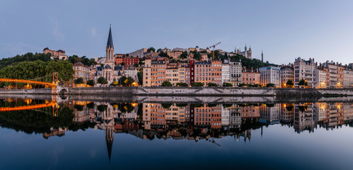Paul-Couturier Footbridge over Saone river against buildings during sunset