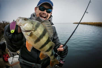 Happy angler with perch fishing trophy.