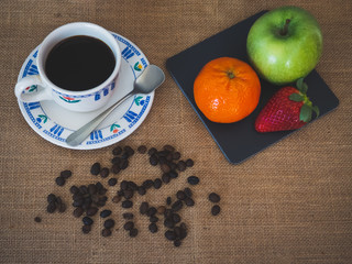 Breakfast of a porcelain coffee cup, coffee beans, an old spoon and a plate with one green apple, one tangerine and one strawberry on a vintage burlap background