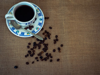 Breakfast of a porcelain coffee cup, an antique spoon and coffee beans on a vintage burlap background
