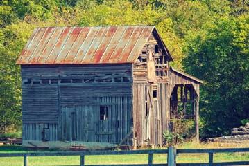 Run down old barn building in green field