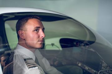 Side view of confident pilot flying flight simulator seen through windshield