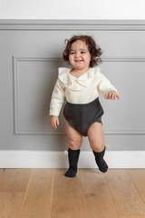 Cute happy baby girl dancing on hardwood floor against wall at home