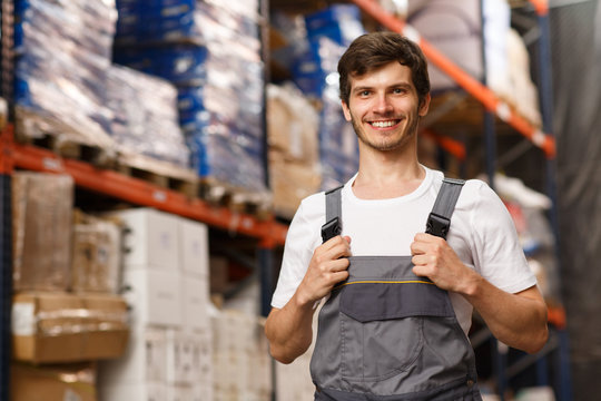 Good looking loader of warehouse posing, smiling and looking at camera. Cheerful worker standing and holding uniform by hands. Forklift and shelves with goods on background.