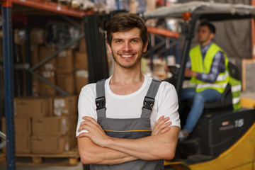 Front view of handsome workerof warehouse smiling, posing and looking at camera. Specialist wearing in acid green reflective waistcoat, loader operating forklift on background.