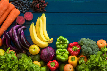 Flat lay of fresh  fruits and vegetables with copy space, Different fruits and vegetables for eating healthy, Colorful fruits and vegetables on blue plank