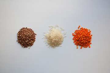 Raw buckwheat, basmati rice and red lentils isolated on white background from a high angle view