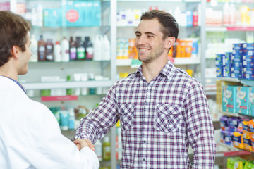 Good looking customer in checked shirt looking at male pharmacist and shaking hands with him. Man smiling after buying medicines. Background of drugstore and shelves with medicines.