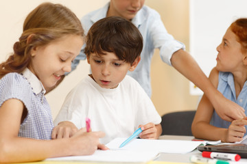 Curious little student of modern school sitting near girl in looking her copybook and asking her in classroom. Schoolboy talking with classmate while learning new material an school.