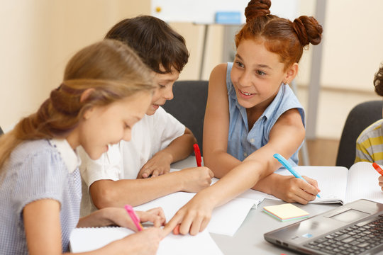 Curious schoolgirl sitting at table near classmates and pointing in copybook of friend with finger in classroom. Pupils working in groups and enjoying learning process. Friendly atmosphere concept.