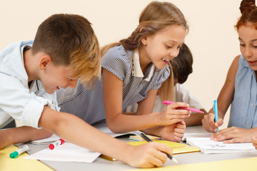 Interested schoolgirl working in team with classmates during lesson in school. Cute student talking with friends, writing in copybook and doing tasks in classroom. Concept of modern education.