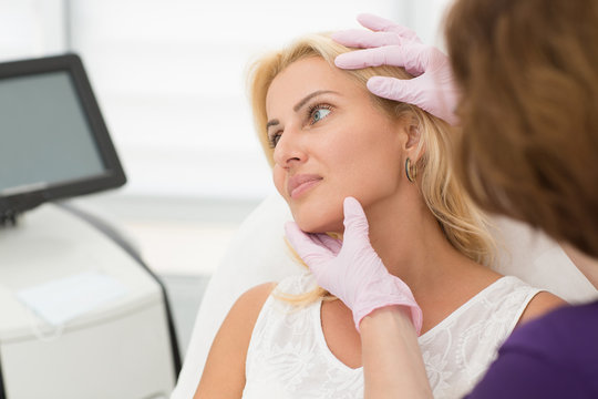 Side view of attractive woman during appointment with doctor at cosmetology office. Blonde sitting on coach and looking away while female beautician in gloves examining skin after procedure.