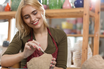 Beautiful woman in red apron carving with knife on earthenware in workshop. Professional female potter smiling and enjoying process of making clay bowl. Concept of pottery and handicraft.