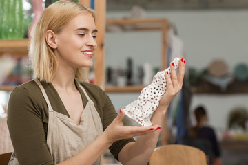 View from side of female potter admiring good result of work in workshop. Attractive blonde keeping in hands clay thing, looking at it and smiling. Concept of favorite hobby and ceramics.