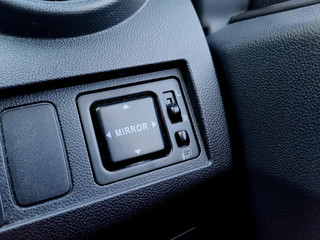 Close up image of side mirror button panel beside driver seat.