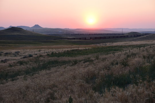 Empty high plains landscape of hills and coal train at sunset in the Powder River Basin in Wyoming, USA.