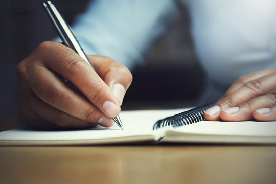 hand of woman holding pen with writing on notebook in office