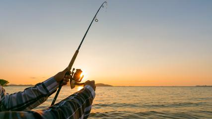 Fishing rod wheel closeup, man fishing with a beautiful sunrise behind him Wall mural