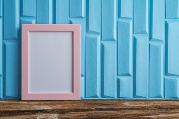 Pink photo frame on old wooden table over blue wallpaper background