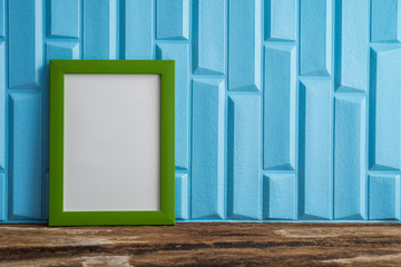 Green photo frame on old wooden table over blue wallpaper background