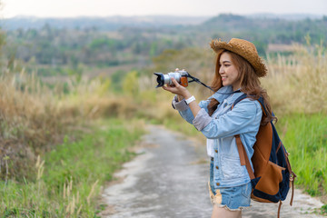 tourist woman taking photo with her camera in nature