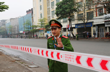 A policeman gestures behind a police line at a road block as the motorcade of North Korea's leader Kim Jong Un travels towards his hotel, ahead of the North Korea-U.S. summit in Hanoi
