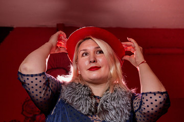 Fat woman wearing a hat in a dark room with red light. Gangsters style