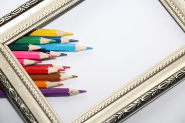 Vintage frame for paintings and colored pencils on a white background. Many colored pencils.