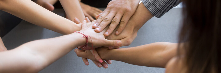Horizontal close up image caucasian people holding stacking hands together