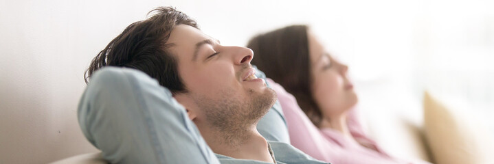 Horizontal photo married couple with closed eyes resting on couch