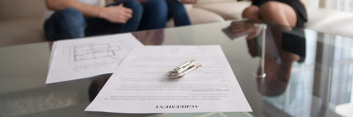 Horizontal image couple meets with realtor for signing rental agreement
