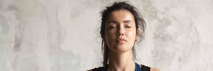 Horizontal image beautiful woman face with closed eyes practicing yoga