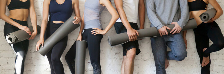 Group people wearing activewear holding yoga mats standing near wall  Wall mural