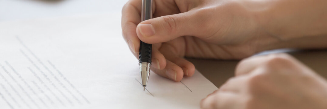 Closeup male hand holding pen put signature on official document