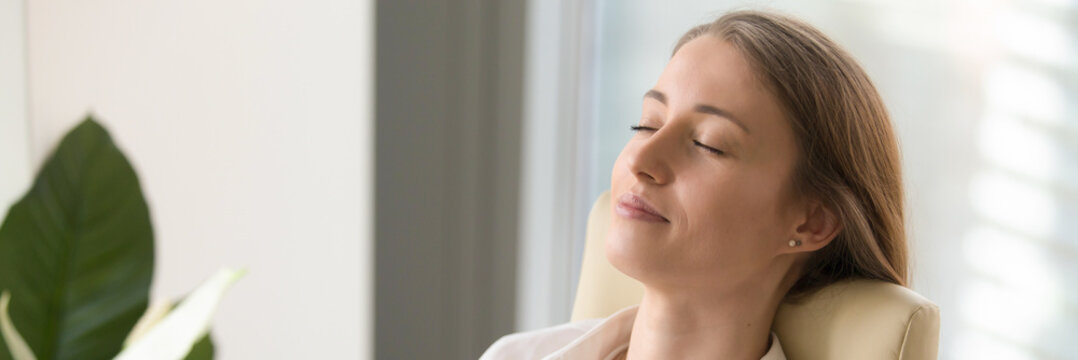 Horizontal image young woman closing eyes resting sitting on chair