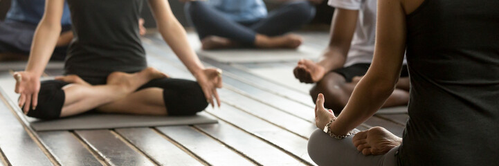 Horizontal photo group people sitting in lotus position practicing yoga