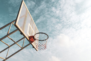 Copy space of outdoor basketball court on blue sky and white cloud background.