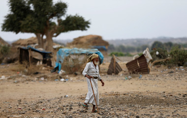 A man walks in an improvised camp for internally displaced people near Abs of the northwestern province of Hajja