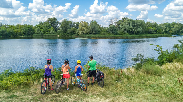 Family on bikes cycling outdoors, active parents and kids on bicycles, aerial view of happy family with children relaxing near beautiful river from above, sport and fitness concept