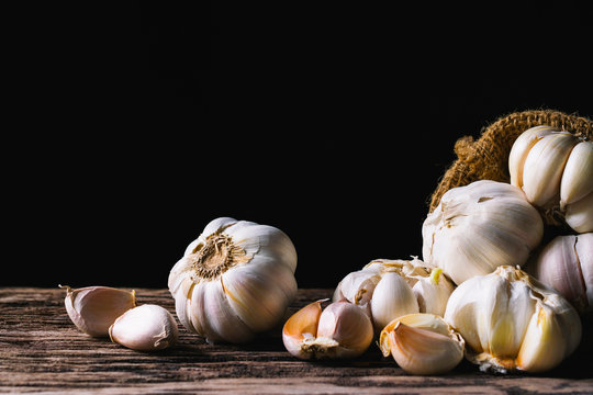 Closeup garlic on wooden texture on for cooking on dark background.