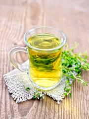 Tea of thyme in mug on board