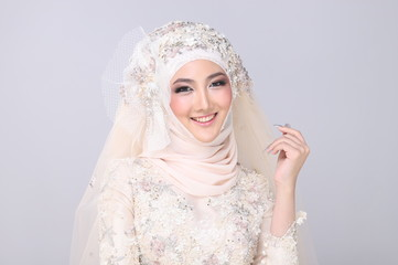 Asian Charming muslim arabic bride in Lace Bead Embroidery creammy yellow wedding dress and hijab headscarf, close-up on Fashion Make up Eyes Face, studio lighting grey background isolated.