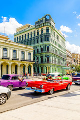 Foto op Canvas Havana Old colonial buildings across the road with driving retro red ca