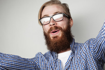 Portrait of  young bearded  man taking selfie and holding camera